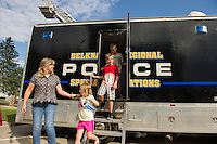 Donna Mauzy gives Sophia Benwell a hand as they exit their tour of the Belknap Regional Police Special Operations Unit during Belmont's National Night Out at the Mill and Pavilion Tuesday evening.  (Karen Bobotas/for the Laconia Daily Sun)