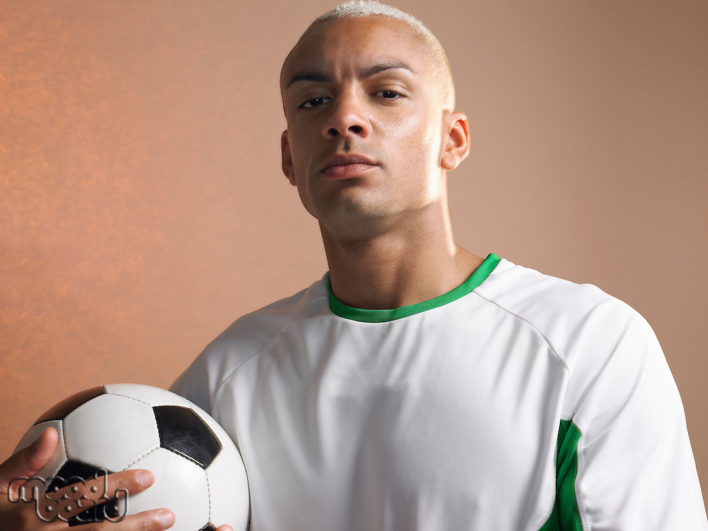 Football player holding ball portrait
