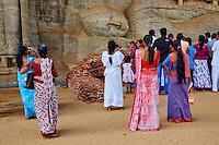 Sri Lanka, province du Centre-Nord, cité historique de Polonnaruwa, classée au Patrimoine Mondial de l'UNESCO, Gal Vihariya (Gal Vihara), ensemble des quatres statues de Bouddha taillées dans la roche, bouddha couché, pelerins en devotion // Sri Lanka, Ceylon, North Central Province, ancient city of Polonnaruwa, UNESCO World Heritage Site, Gal Vihara, reclining Buddha, pilgrims