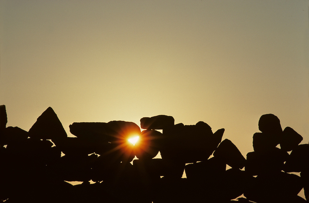Ireland, Sun shines through rock wall near town of Lettermore in County Galway on autumn evening