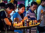 31 MAY 2017 - CHACHOENGSAO, THAILAND: People light prayer candles at Wat Sothon (also spelled Sothorn) in Chachoengsao, Thailand. The temple is one of the largest and most visited in Thailand. People make merit by paying to wrap the Buddha statues in orange robes. The temple is most famous because people leave hard boiled eggs as an offering at the temple. They ask for business success or children and leave hundreds of hard boiled eggs.      PHOTO BY JACK KURTZ