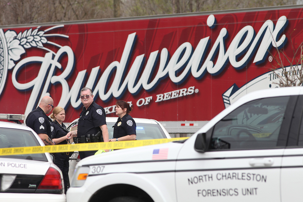 ANDREW KNAPP/STAFF -- March 18, 2013 -- North Charleston police officers work near a Budweiser truck after a delivery man was shot Monday afternoon outside the Neighbor Store at 1740 E. Montague Ave.