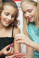 Young girl applying nail polish to friends fingernails