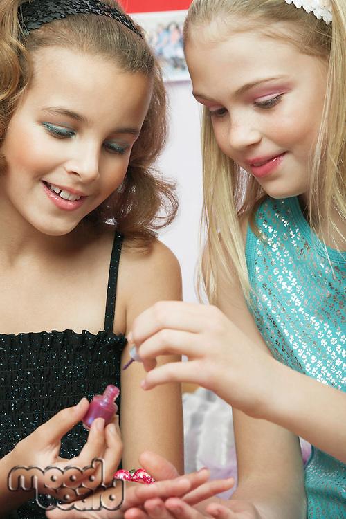 Young girl applying nail polish to friends fingernails