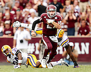 Oct 20, 2012; College Station, TX, USA; Texas A&M Aggies quarterback Johnny Manziel (2) runs past LSU Tigers safety Micah Eugene (34) and defensive tackle Bennie Logan (18) during the third quarter at Kyle Field. Mandatory Credit: Thomas Campbell