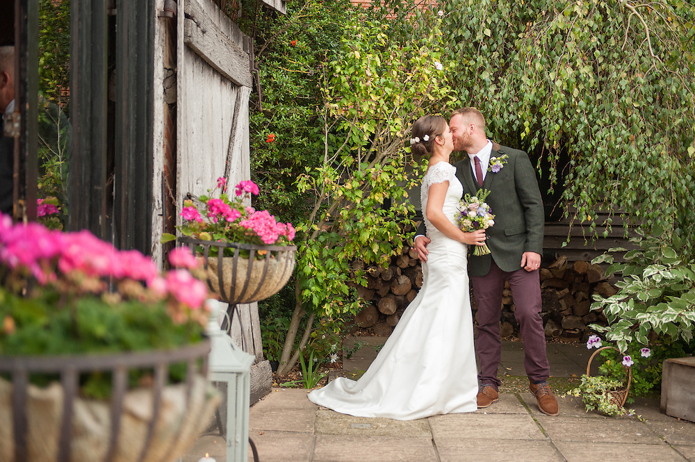 A staged portrait of Craig and Liz outside their reception venue. Preferring a natural approach to posing I roughly set up such that I could see the lovely barn door and the flower baskets in the foreground and left them to it. <br />