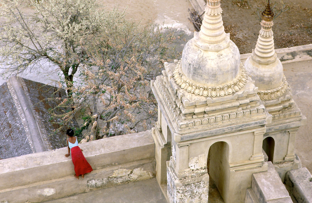 A young Burmese Girl gazes out from the terrace of a giant Pagoda, Bagan (Pagan), Burma (Myanmar)
