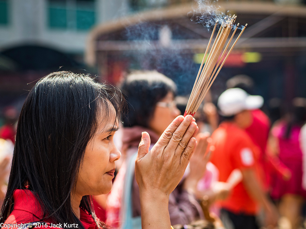 """08 FEBRUARY 2016 - BANGKOK, THAILAND: A woman prays during Chinese New Year observances at Kuan Yim Shrine in Bangkok's Chinatown district, during the celebration of the Lunar New Year. Chinese New Year is also called Lunar New Year or Tet (in Vietnamese communities). This year is the """"Year of the Monkey."""" Thailand has the largest overseas Chinese population in the world; about 14 percent of Thais are of Chinese ancestry and some Chinese holidays, especially Chinese New Year, are widely celebrated in Thailand.       PHOTO BY JACK KURTZ"""