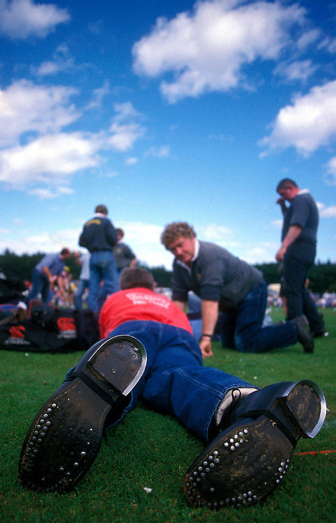 Participants wear special shoes for more traction during the tug-o-war match at the Highland Games in St. Andrews, Scotland.