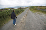 Model released young boy walking along country lane, west coast of Ireland, County Clare, near Ballyvaughan