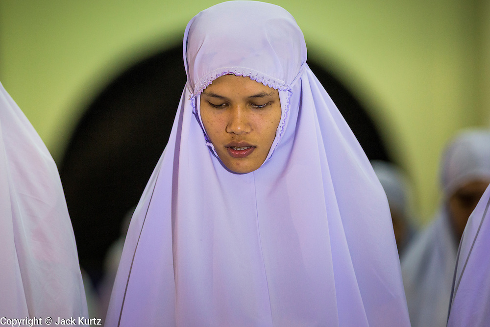 09 JULY 2013 - PATTANI, PATTANI, THAILAND:  Women pray in Pattani Central Mosque in Pattani, Thailand, Tuesday night on the first night of Ramadan. Ramadan is the ninth month of the Islamic calendar, and the month in which Muslims believe the Quran was revealed. Muslims believe that the Quran was sent down during this month, thus being prepared for gradual revelation by Jibraeel (Gabriel) to the Prophet Muhammad. The month is spent by Muslims fasting during the daylight hours from dawn to sunset. Fasting during the month of Ramadan is one of the Five Pillars of Islam.   PHOTO BY JACK KURTZ