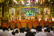 17 OCTOBER 2012 - BANGKOK, THAILAND:    Chinese-Thais participate in a prayer service during the Vegetarian Festival at Wat Mangkon Kamalawat, one of the largest Chinese shrines in Thailand. The Vegetarian Festival is celebrated throughout Thailand. It is the Thai version of the The Nine Emperor Gods Festival, a nine-day Taoist celebration celebrated in the 9th lunar month of the Chinese calendar. For nine days, those who are participating in the festival dress all in white and abstain from eating meat, poultry, seafood, and dairy products. Vendors and proprietors of restaurants indicate that vegetarian food is for sale at their establishments by putting a yellow flag out with Thai characters for meatless written on it in red.      PHOTO BY JACK KURTZ