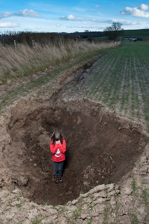Young girl in deeply eroded cereal field, Angus, Scotland.Europe