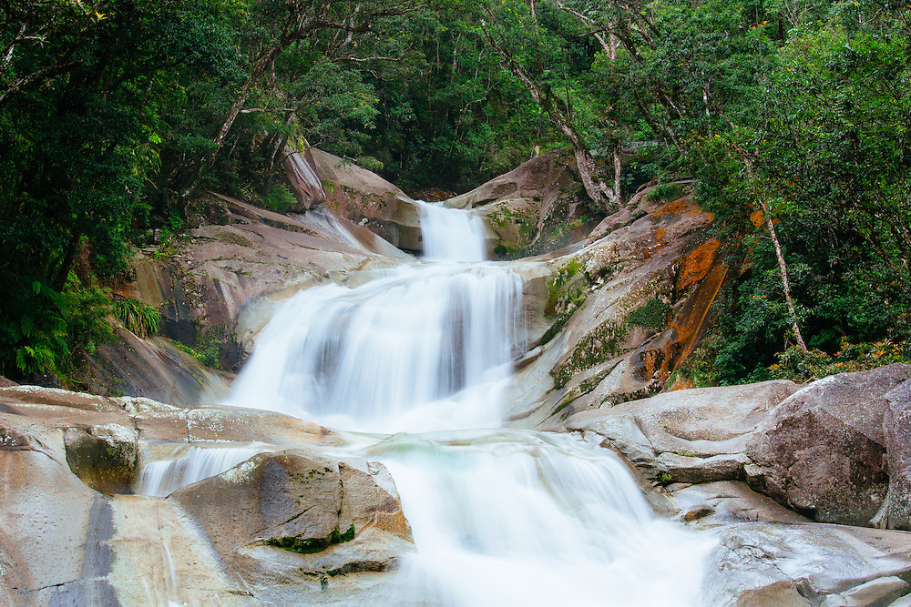 Smoothed granite surfaces and rushing water of Josephine Falls surrounded by lush World Heritage listed tropical rainforest. Wooroonooran National Park.