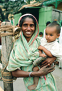 Mother holding child, street scene, India