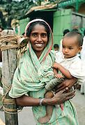 Mother holding child, street scene, India
