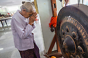 24 MAY 2013 - MAE SOT, THAILAND:    A woman prays after hitting a prayer gong at Wat Chum Phon Khiri on Visakha Puja Day. Visakha Puja (Vesak) marks three important events in the Buddha's life: his birth, his attainment of enlightenment and his death. It is celebrated on the full moon of the sixth lunar month, usually in May on the Gregorian calendar. This year it is on May 24 in Thailand and Myanmar. It is celebrated throughout the Buddhist world and is considered one of the holiest Buddhist holidays.    PHOTO BY JACK KURTZ