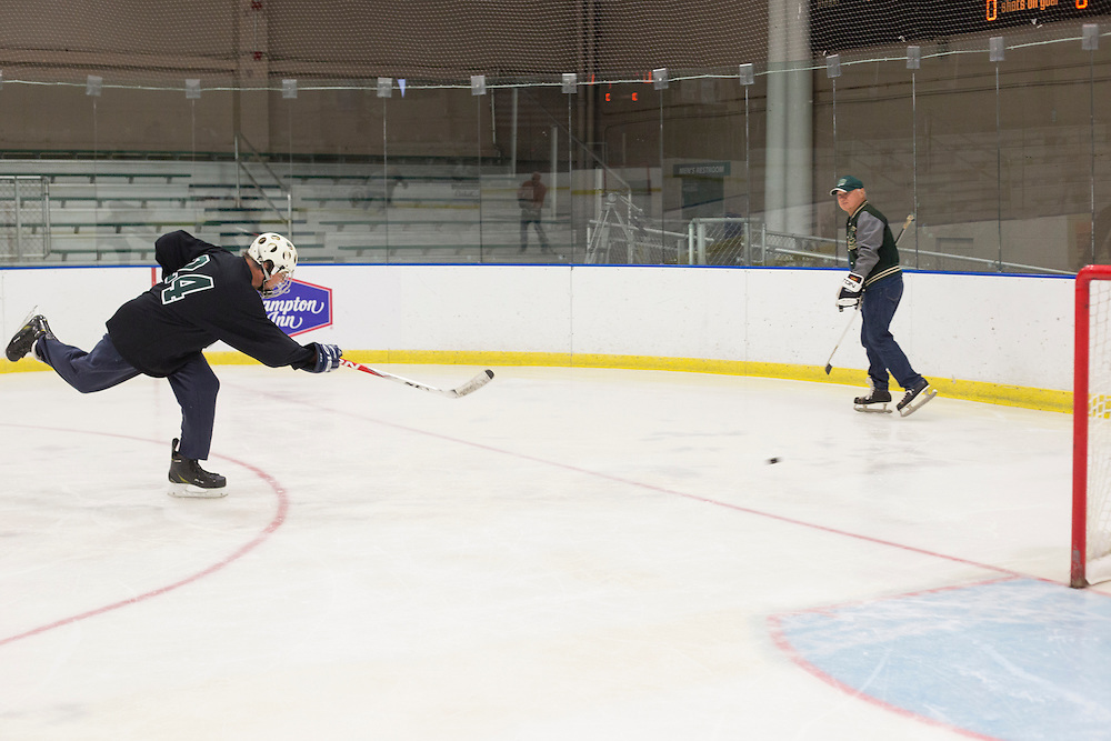 Alex MacNicol, left, shoots the puck at Tom Gosiorowski during the 1960s hockey alumni reunion at Bird Arena on October 1, 2016.