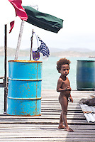 Young boy on a wooden boardwalk in the water village of Hanoabada, near Port Moresby, Papua New Guinea