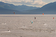 Kite surfers ride waves caused by the bore tide on Turnagain Arm at Windy Point outside Anchorage, Alaska.