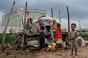 A Cham family sits in front of their home in Phnom Penh, Cambodia, with the Sokha hotel in the background. The newly completed hotel had previously worked with the government of Cambodia to evict the Cham community from their land.