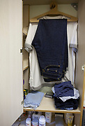 Prison issue clothes hanging in a wardrobe in a cell at HMP Kingston. Portsmouth, United Kingdom.