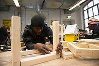DEU, Deutschland, Germany, Berlin, 17.12.2015: Flüchtlinge arbeiten in einer Werkstatt der Flüchtlings-Initiative der Handwerkskammer, arrivo Berlin, in der Innung für Metall- und Kunststofftechnik. El Alhagie Gailou aus Ghana beim Arbeiten an einem Tisch.