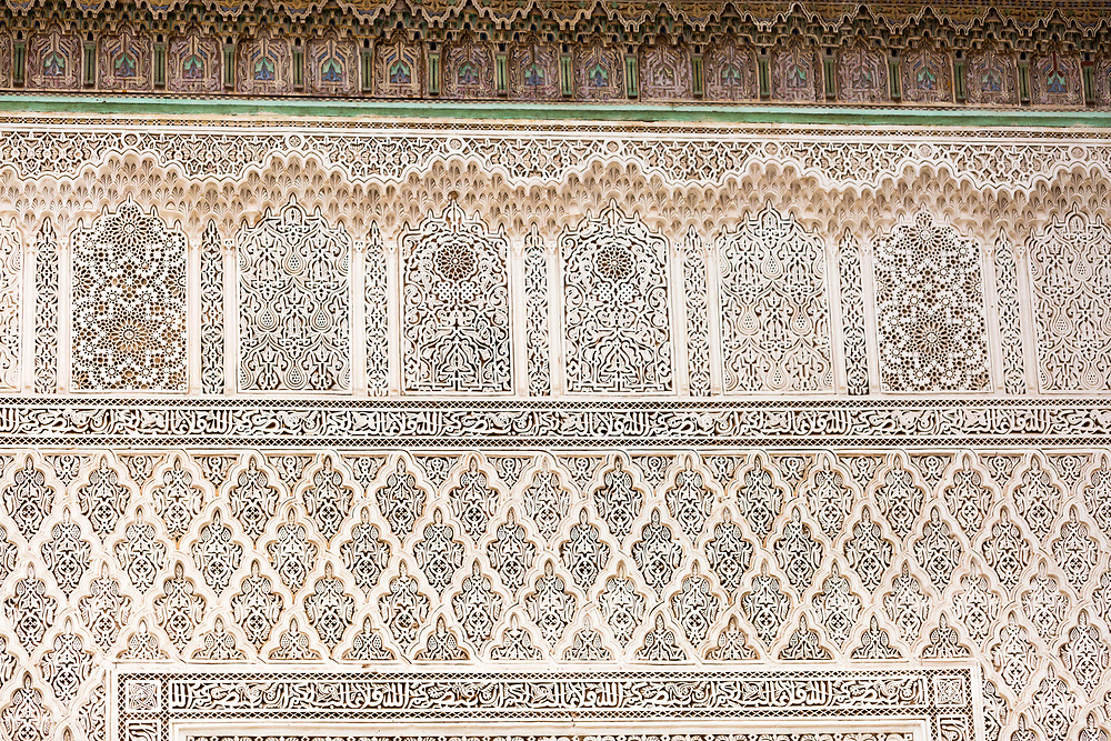 MARRAKESH, MOROCCO - 19TH APRIL 2016 - Close up of intricate and detailed stone carvings with Arabic scripture and geometric shapes lining the Zaouia / zawiya burial tomb shrine site of Sidi Bel Abbas (Abu al-Abbas) al-Sabti, Marrakesh, Morocco.