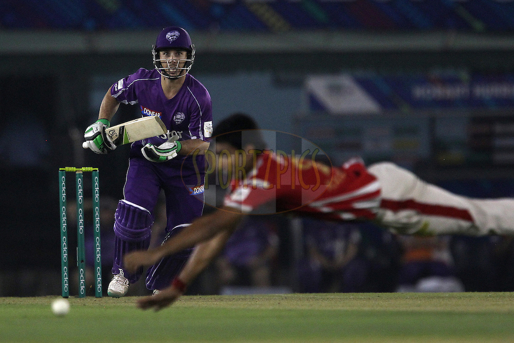 Jon WELLS of the Hobart Hurricanes looks on as Karanveer SINGH of the Kings XI Punjab tries to stop the ball during match 2 of the Oppo Champions League Twenty20 between the Kings XI Punjab and the Hobart Hurricanes held at the Punjab Cricket Association Stadium, Mohali, India on the 18th September 2014<br /> <br /> Photo by:  Ron Gaunt / Sportzpics/ CLT20<br /> <br /> <br /> Image use is subject to the terms and conditions as laid out by the BCCI/ CLT20.  The terms and conditions can be downloaded here:<br /> <br /> http://sportzpics.photoshelter.com/gallery/CLT20-Image-Terms-and-Conditions-2014/G0000IfNJn535VPU/C0000QhhKadWcjYs
