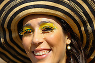 A Brazilian fan in a big hat with yellow and green eye makeup outside the ground before the 2014 FIFA World Cup last 16 match at Maracana Stadium, Rio de Janeiro, Brazil.<br /> Picture by Andrew Tobin/Focus Images Ltd +44 7710 761829<br /> 28/06/2014
