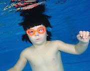 Three year old child swims underwater in a pool