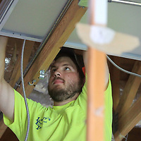 Drew Bruce, an employee with Lackey's Electrical in Tupelo, disconnects lighting for its removal as crews work to demo the interior of the CVB office in Tupelo on Tuesday.