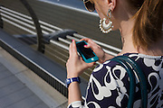 A young woman walks over London's Millennium Bridge while using her smartphone.