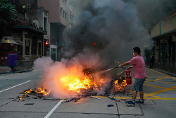 Hong Kong. 1 October 2019. After a peaceful march through Hong Kong Island by an estimated 100,000 pro democracy supporters, violent flared up at Tamar, Admiralty and moved through Wanchai district. Police used teargas and baton rounds and water cannon. Hard core group lit fires, threw bricks and Molotov cocktails at police. Violence continues into evening. Local man uses fire extinguisher on fire set on street in Wanchai.  Iain Masterton/Alamy Live News.