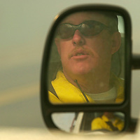 Polk County, Fla firefighter Ken Jolly peers out through the smoke from his brush truck to watch a backfire that was set  in efforts to control a wildfire that burned up around 200 acres in Polk County, Fla. on Friday, Jan., 26, 2000 near Polk City, Fla. (AP Photo/Scott Audette)