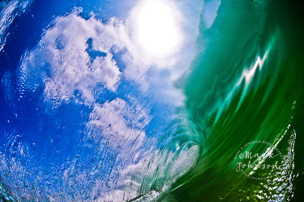 The puffy white clouds, blue sky, and sun in the sky showing through the falling curtain of the wave. In my years as a wave photographer, this is the first time I've been able to capture the sky through a wave.  This is a very unique photograph and will match any decor.
