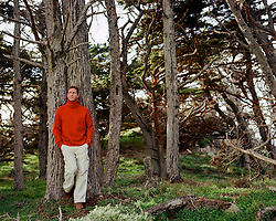 man in a turtleneck sweater leaning against trees in Point Lobos State Park in Northern California