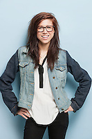 Portrait of happy young woman with hands on hips standing against light blue background