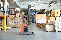 Man operating fork lift truck in distribution warehouse
