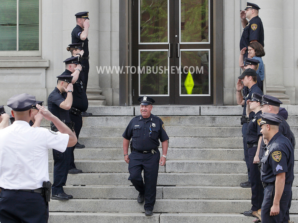 Middletown police salute officer Michael Canonico, center,  during  a ceremony marking the final day of Canonico's 32 years on the department. Middletown police Chief Ramon Bethencourt is at left.