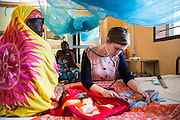 Dr Siobhan Neville examines a baby on the NICU (Neonatal Intensive Care Unit) Ward. St Walburg's Hospital, Nyangao. Lindi Region, Tanzania.