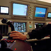 Joystick controller at BAE Systems Hawk jet aircraft simulator test a Red Arrows pilot at the fast-jet flying training centre, RAF Valley, Anglesey, Wales. All fast-jet pilots are required to complete an emergency drill every six months. The pilot is seated in his ejector seat as if in a real jet using back-projected computer graphics representing a generic landscape below. Each aviator proves they can cope with a series of failures that operators select: Engine, hydraulic failure or bird strike.  Apart from the aircraft fuselage, the high-tech facility loads malfunctions on a pilot that he could experience in reality. The version of Hawk that the Red Arrows fly is actually a primitive piece of equipment, without computers or fly-by-wire technology.