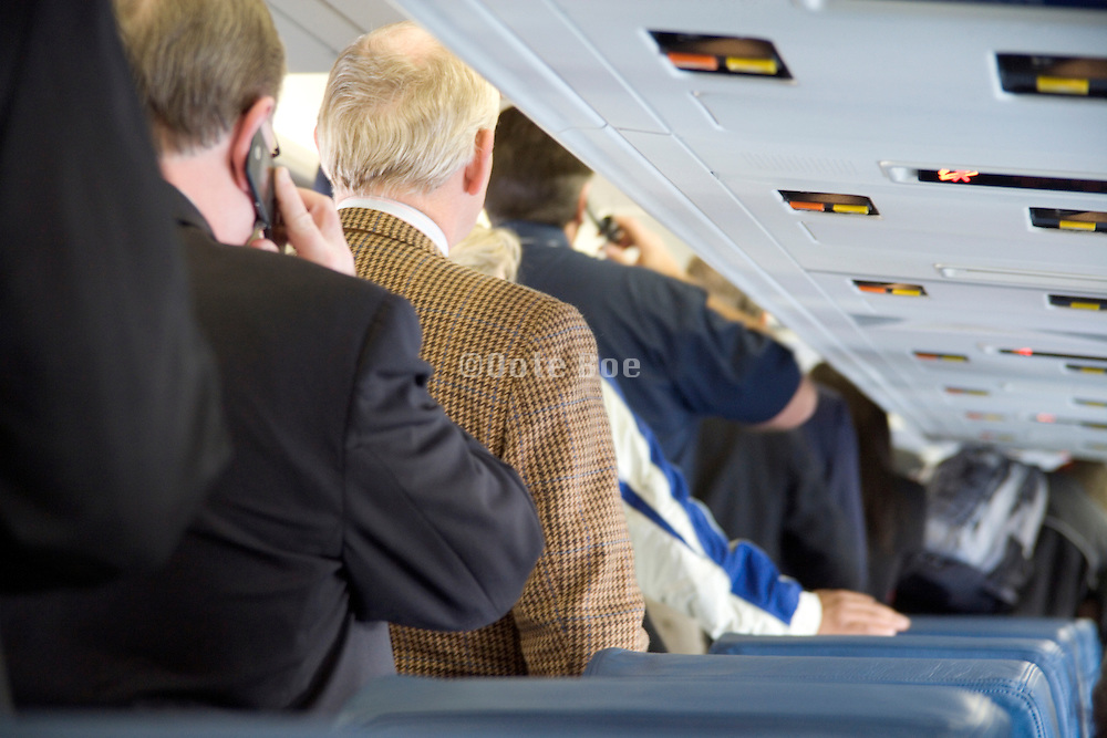 businessman waiting in the aisle to leave the airplane