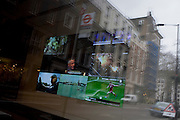 Screens from assorted media seen through a London window with street outside reflected.