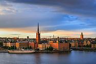 Riddarholmen i skymning med uppklarnande efter häftig regnskur vid Riddarfjärden i Stockholm