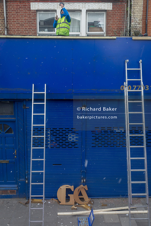 A workman stands on a flat roof to hold up his phone while installing new lettering to a shop front in Camberwell, on 27th February 2018, in London, England.
