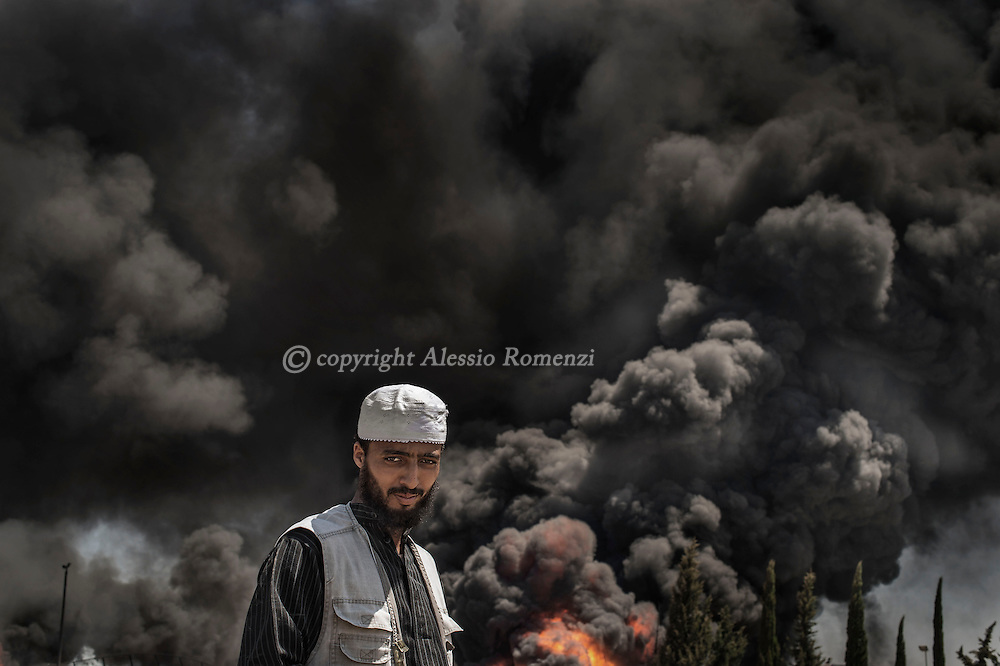 Gaza Strip: A Palestinian man stands nearby Nusairat power plant as thick black smoke billowed from it on July 29, 2012.<br /> Nusairat power plant is the main source of electricity and the heavy damages reported after the overnight Israeli strikes put in danger of energy shortage the entire Gaza strip.ALESSIO ROMENZI