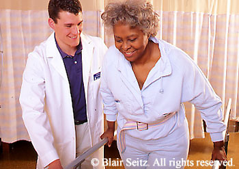 Medical Physical Therapy, Patient and Therapist, Caring Therapist Male Physical Therapist Works with Patient Male Physical Therapist with Patient on Parallel Bars