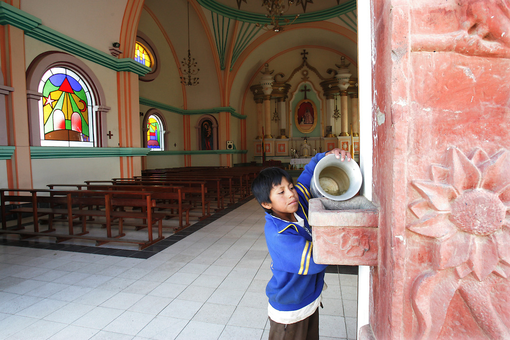 "A boy adds holy water before mass  at at church that Father Sebastian Obermaier built in El Alto, Bolivia. a town he has lived in for 27 years .  ""I don't feel Bolivian, I feel Aymara"" he says, referring to the Aymara indigenous population that makes up more than 80% of El Alto. Father Obermaier has been designing and building churches in El Alto for the past 10 years, with a goal of building one church for every 10,000 inhabitants of the city, which currently has nearly 700,000 people living in it.  Everyone that visits Bolivia can see his numerous churches from the window of their airplane as it lands in El Alto.  The churches are marked by a style unique to Father Obermaier, that mixes indigenous symbols with tall towers and bright colors, that leave every church looking different, as if they were straight out of a children's pop-up book."
