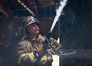 A firefighter sprays water at the ceiling of a still burning house.